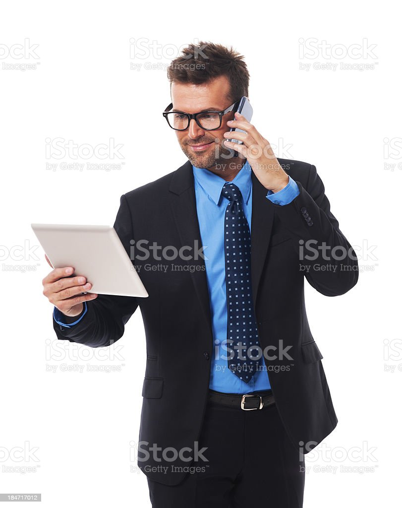 Busy businessman working on tablet and mobile phone royalty-free stock photo