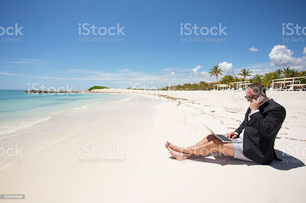 Busy businessman working on the beach stock photo