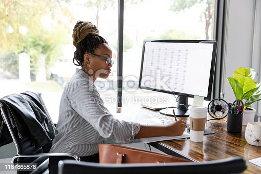 A mid adult African American businesswoman concentrates while working in her office.