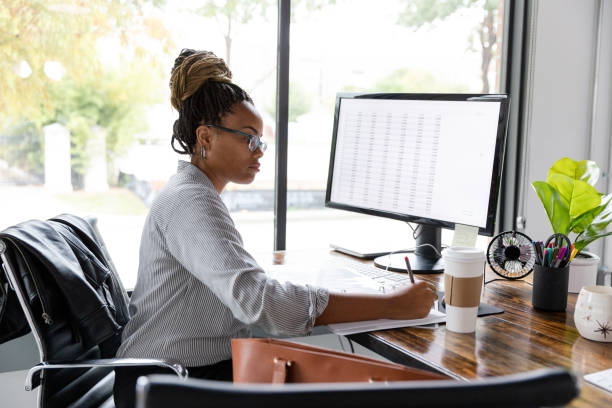 Busy businesswoman concentrates while working at her desk stock photo