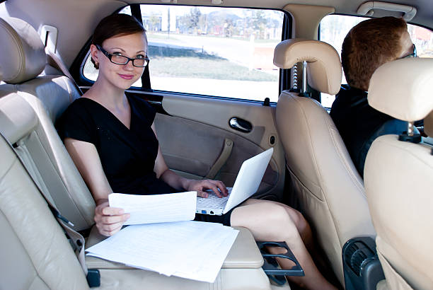 busy businesswoman with document and laptop in car - limousine service stock photos and pictures