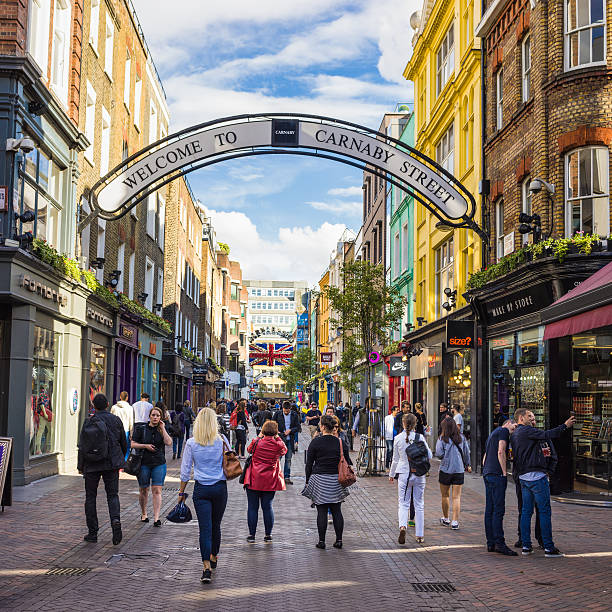Busy Carnaby Street in London London, UK - May 22, 2014: People on Carnaby Street in the Soho area of London. The popular shopping street was pedestrianised in 1973. carnaby street stock pictures, royalty-free photos & images