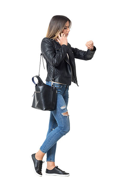 busy casual girl on the phone checking time - druck jeans stock-fotos und bilder