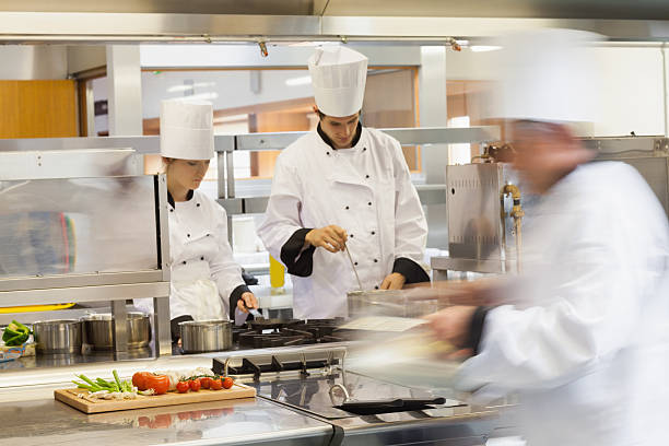 busy chefs at work in the kitchen - busy restaurant kitchen stock pictures, royalty-free photos & images