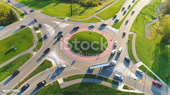 Busy city roundabout intersection at sunrise rush hour, aerial view.