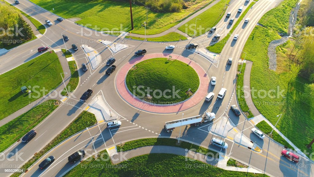 Busy city roundabout intersection at sunrise rush hour. stock photo