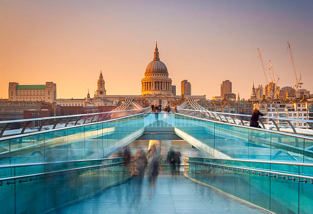 Busy commuters on their way home in London Blurred motion view over the Millennium footbridge looking towards St. Paul's Cathedral at sunset footbridge stock pictures, royalty-free photos & images