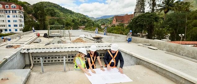 Shot of construction workers and architect  reviewing blueprint at construction site