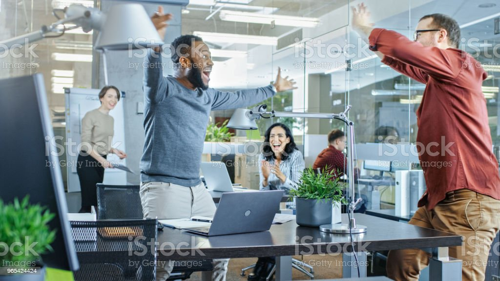 Busy Corporate Office, Man Met Old Friend and Jumping with Happiness, Gives High-Five to His Friend. Everybody is Happy. zbiór zdjęć royalty-free