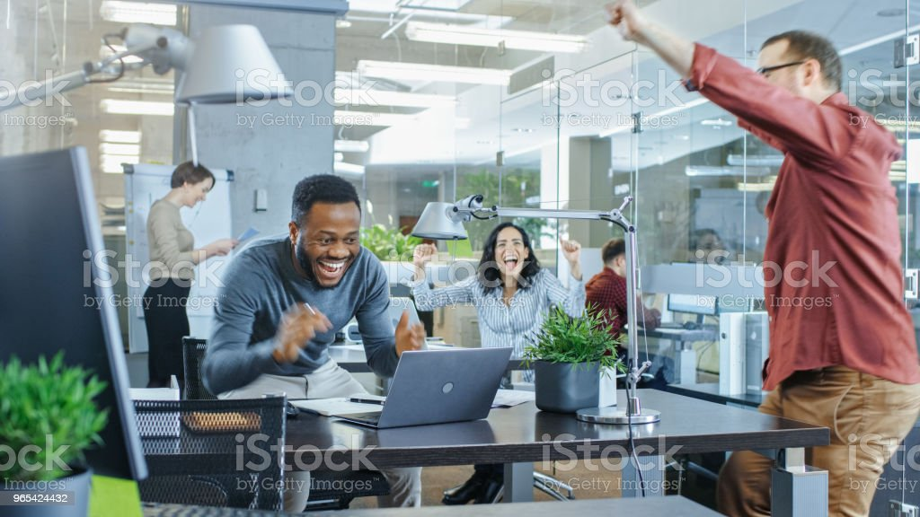 Busy Corporate Office, Man Working on a Laptop Signs Important Contract and Jumps in Celebration, Gives High-Five to His Coworkers. Everybody is Happy. zbiór zdjęć royalty-free