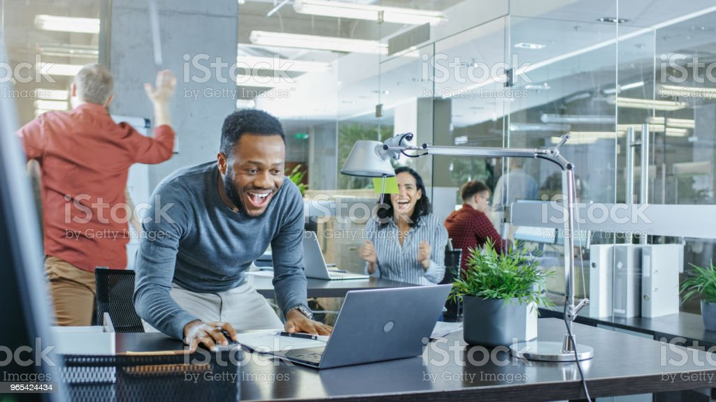 Busy Corporate Office, Man Working on a Laptop Signs Important Contract and Jumps in Celebration, Gives High-Five to His Coworkers. Everybody is Happy. - Zbiór zdjęć royalty-free (Biurko)