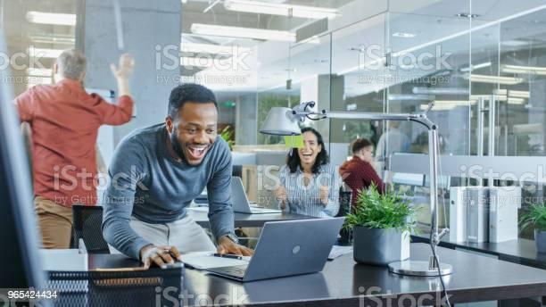 Zajęty Corporate Office Człowiek Pracuje Nad Laptopem Podpisuje Ważny Kontrakt I Skoki W Uroczystości Daje Highfive Do Swoich Współpracowników Wszyscy Są Szczęśliwi - zdjęcia stockowe i więcej obrazów Śmiać się