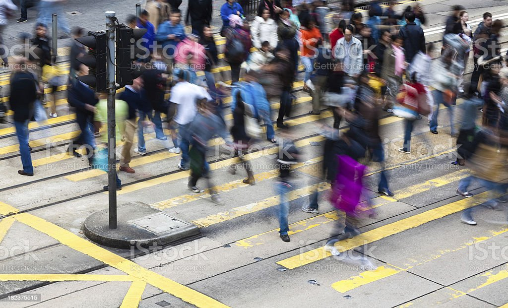 Busy crosswalk with motion blurred pedestrian royalty-free stock photo