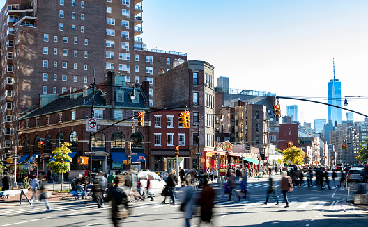Busy crowds of people walking across the street at 7th Avenue in the Greenwich Village neighborhood of New York City NYC