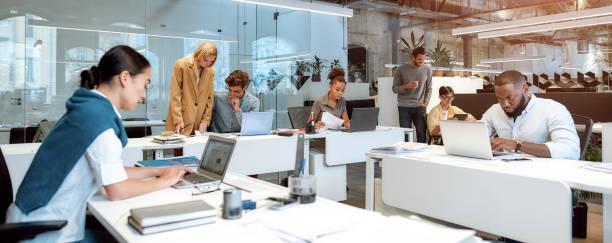 drukke dag. groep van multiraciale zakenmensen die samenwerken in de creatieve co-working ruimte - witte boorden werker stockfoto's en -beelden