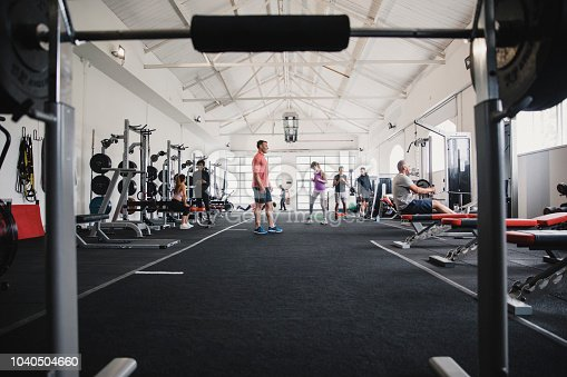 Modern sports gym full of people doing their own workouts.