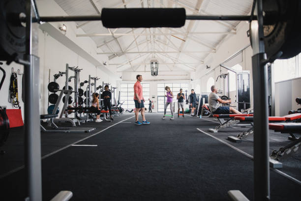 A Busy Day in the Gym Modern sports gym full of people doing their own workouts. health club stock pictures, royalty-free photos & images