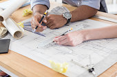 Unrecognizable male and female architects work on a design. Only their hands are seen in the photo.
