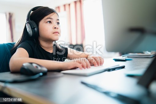 Young girl at home on computer doing home work.