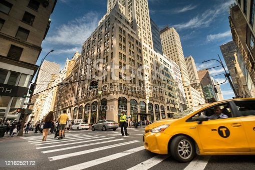 Manhattan, New York - September 21, 2019:  Taxis and people walk across a busy intersection directed by a police woman on Fifth Avenue in downtown Manhattan New York City USA.  5th Avenue is considered a high end luxury shopping district.