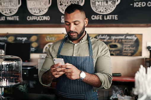 Shot of a young man using a cellphone while working in a cafe
