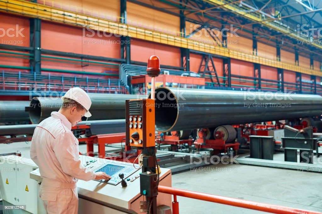 Busy factory engineer managing machine stock photo