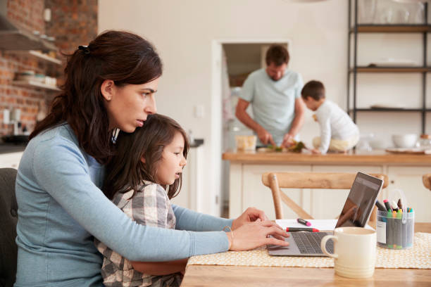 Busy Family Home With Mother Working As Father Prepares Meal stock photo