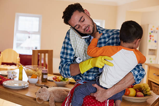 Busy Father Looking After Son Whilst Doing Household Chores stock photo