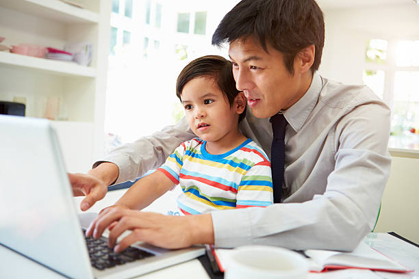 Busy Father Working From Home With Son stock photo