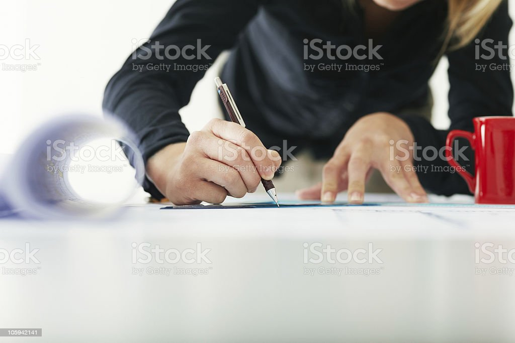 A busy female architect writing at her desk stock photo