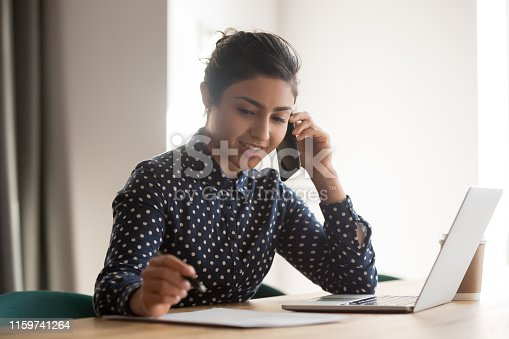 Busy female indian employee talk on smartphone writing on paper document in office, millennial ethnic woman worker consult client over cellphone, handwriting on paperwork using laptop