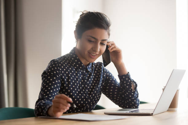 Busy female indian employee talk on cellphone at workplace Busy female indian employee talk on smartphone writing on paper document in office, millennial ethnic woman worker consult client over cellphone, handwriting on paperwork using laptop assistant stock pictures, royalty-free photos & images