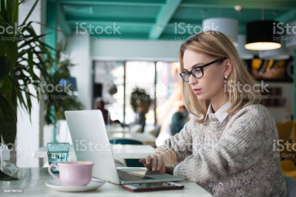 Busy female student preparing for exam in cafe stock photo