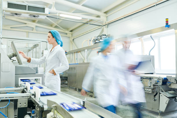 Busy female worker in sterile clothes choosing program on touch screen while operating manufacturing machine producing packaged food, blurred motion of technologists stock photo