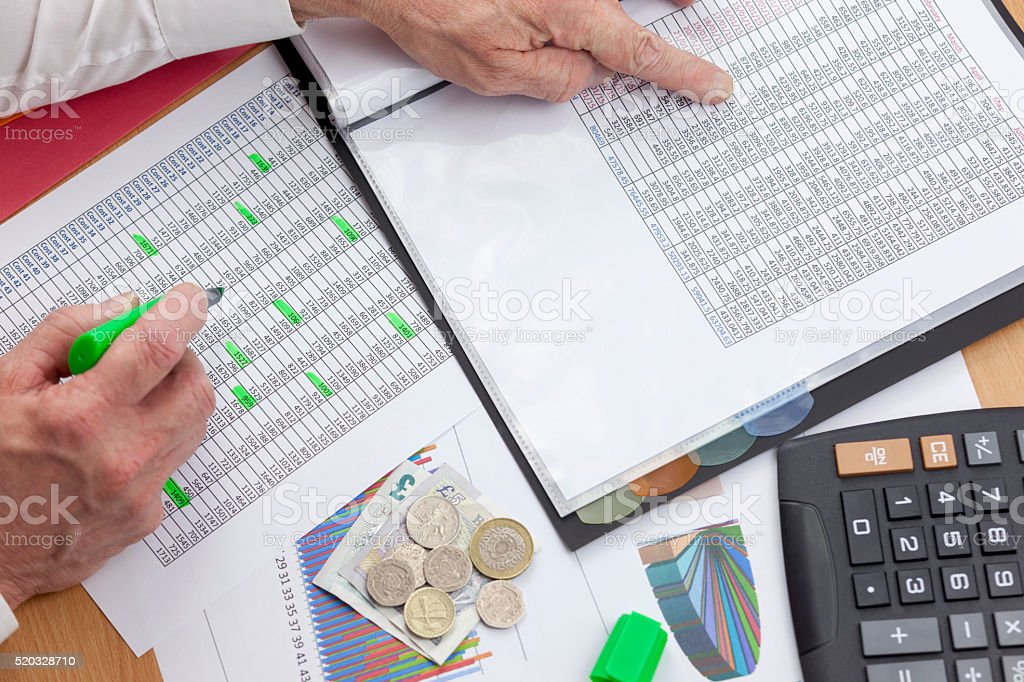 Busy financier at his desk checking two sales reports stock photo