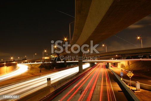 A nightime photo of a busy southern california freeway, with light streaks and a trail from a jetliner