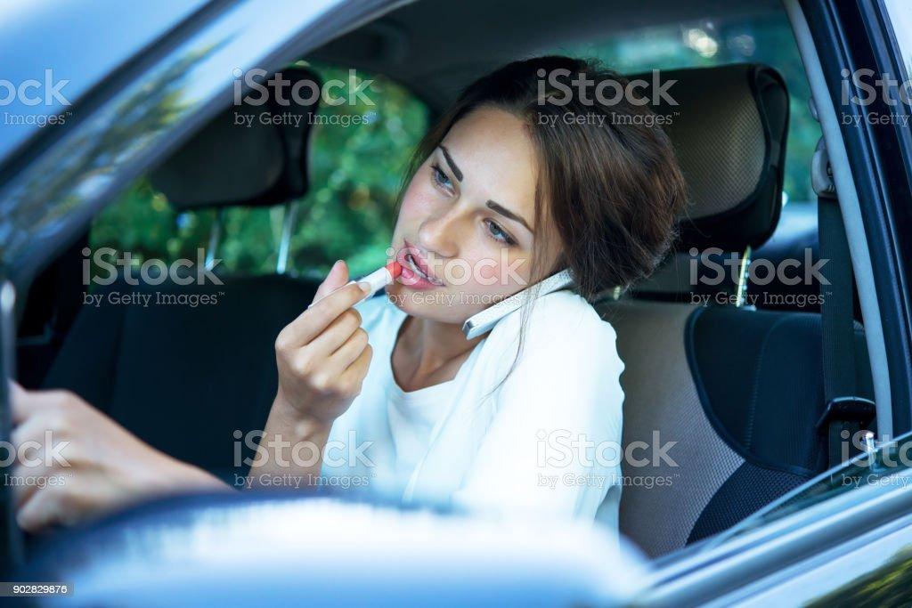 beschäftigt Mädchen mit Lippenstift und Telefon während der Fahrt – Foto