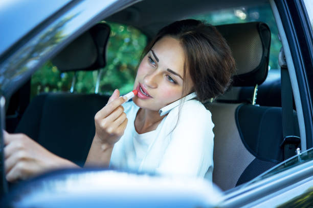 busy girl with lipstick and phone while driving - detraction stock pictures, royalty-free photos & images