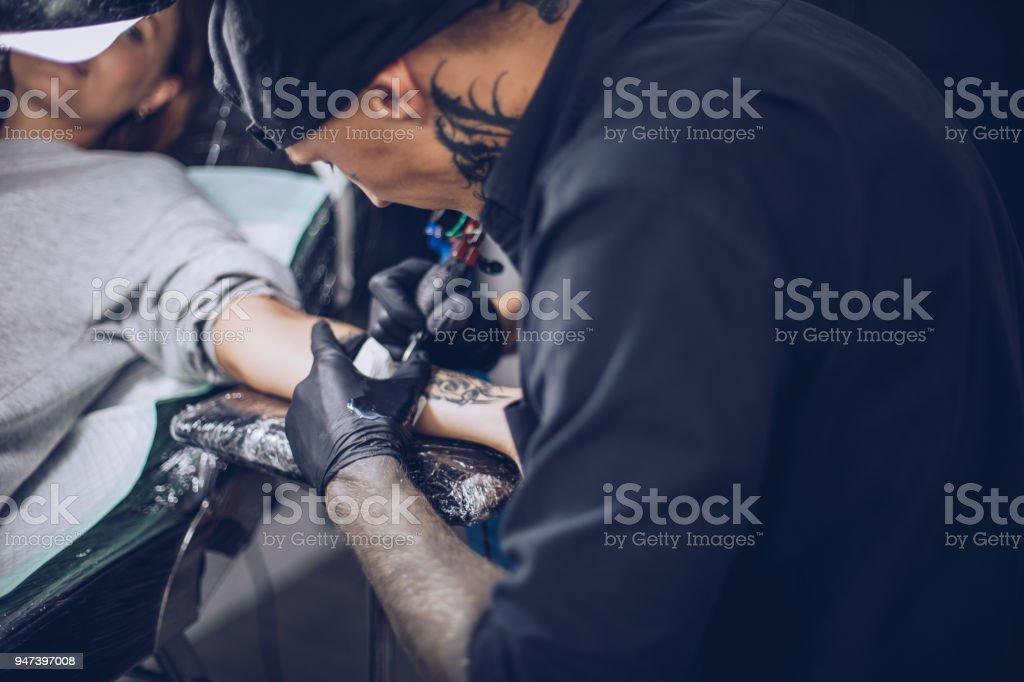 Busy guy tattoo artist stock photo