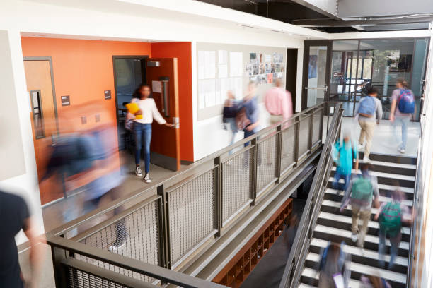 busy high school corridor during recess with blurred students and staff - college foto e immagini stock