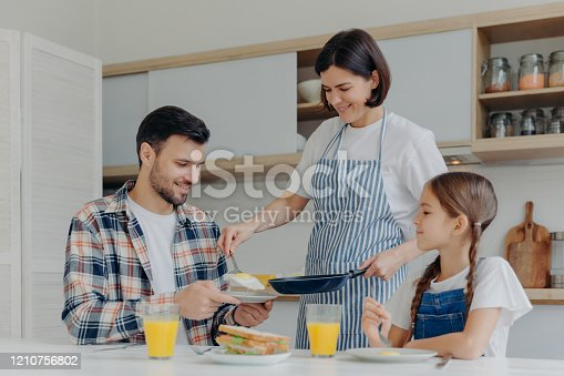 Busy housewife holds frying pan, gives prepared meal to husband and daughter, have delicious breakfast together, sit at kitchen table with glass of juice and sandwich. Happy family eat at home