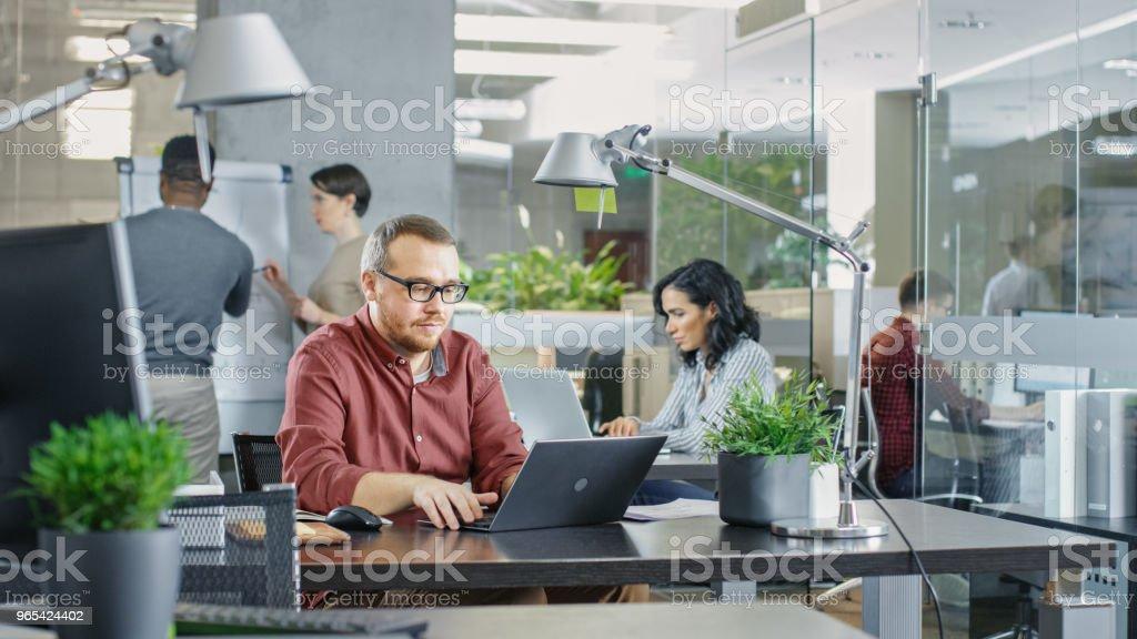 Ocupado escritório corporativo internacional, homem caucasiano que trabalha em sua mesa em um Laptop. No fundo criativos jovens trabalhando. - Foto de stock de Adulto royalty-free