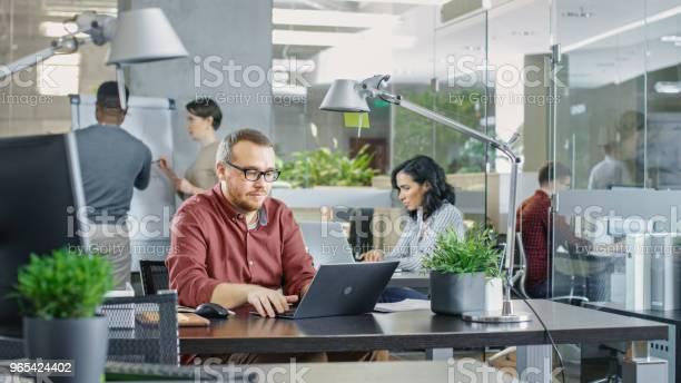 Foto de Ocupado Escritório Corporativo Internacional Homem Caucasiano Que Trabalha Em Sua Mesa Em Um Laptop No Fundo Criativos Jovens Trabalhando e mais fotos de stock de Adulto