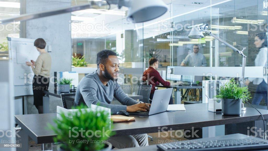 Bureau International occupé, homme afro-américain travaillant à son bureau sur un ordinateur portable, écrit-il en rappel son carnet. À l'arrière-plan les créatifs jeunes travail. - Photo de A la mode libre de droits