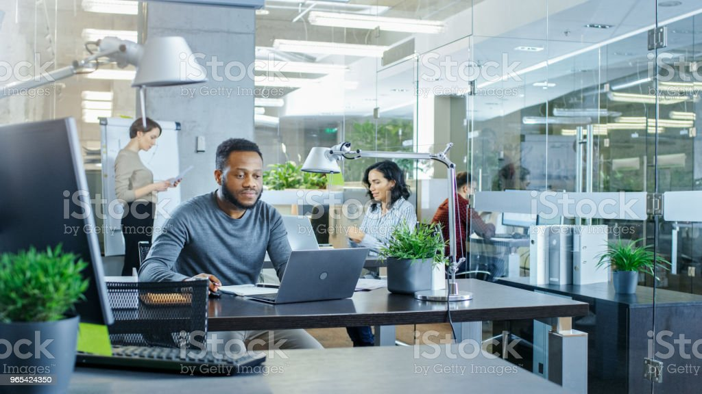 Busy International Office, African-American Man Working at His Desk on a Laptop, in the Background Businesswomen Discuss Relevant Data. Stylish Office with Talented Young People. zbiór zdjęć royalty-free