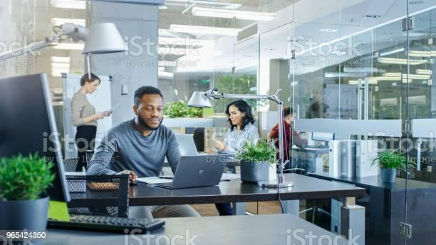 Busy International Office Africanamerican Man Pracy W Jego Biurku Na Laptopie W Tle Businesswomen Dyskutować Odpowiednie Dane Stylowe Biuro Z Utalentowanymi Młodymi Ludźmi - zdjęcia stockowe i więcej obrazów Biurko