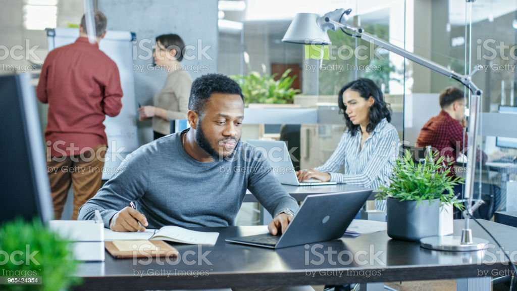 Busy International Office, African-American Man Working at His Desk on a Laptop, He Writes in Reminder His Notebook. In Background Creative Young People Working. zbiór zdjęć royalty-free