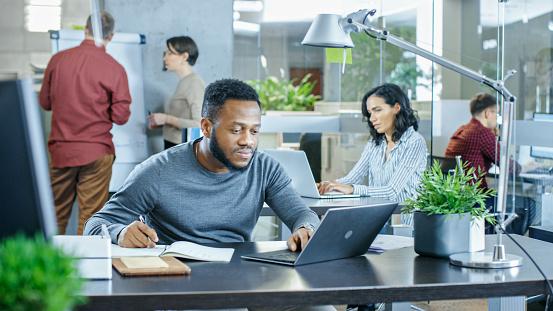 바쁜 국제 사무실 그는 그의 노트북 알리미에 쓴다 노트북에 그의 책상에서 일하고 아프리카계 미국인 남자 백그라운드에서 창조적인 젊은 사람들이 작업 금융에 대한 스톡 사진 및 기타 이미지