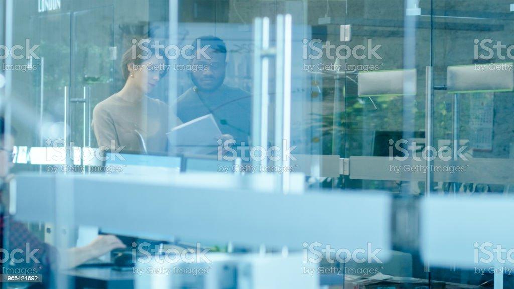 Bureau International occupé, belle caucasien femme montre des Documents à un collègue noir tout en marchant à travers couloir de verre. Dans le groupe diversifié de fond de créatifs collègues de travail. - Photo de A la mode libre de droits
