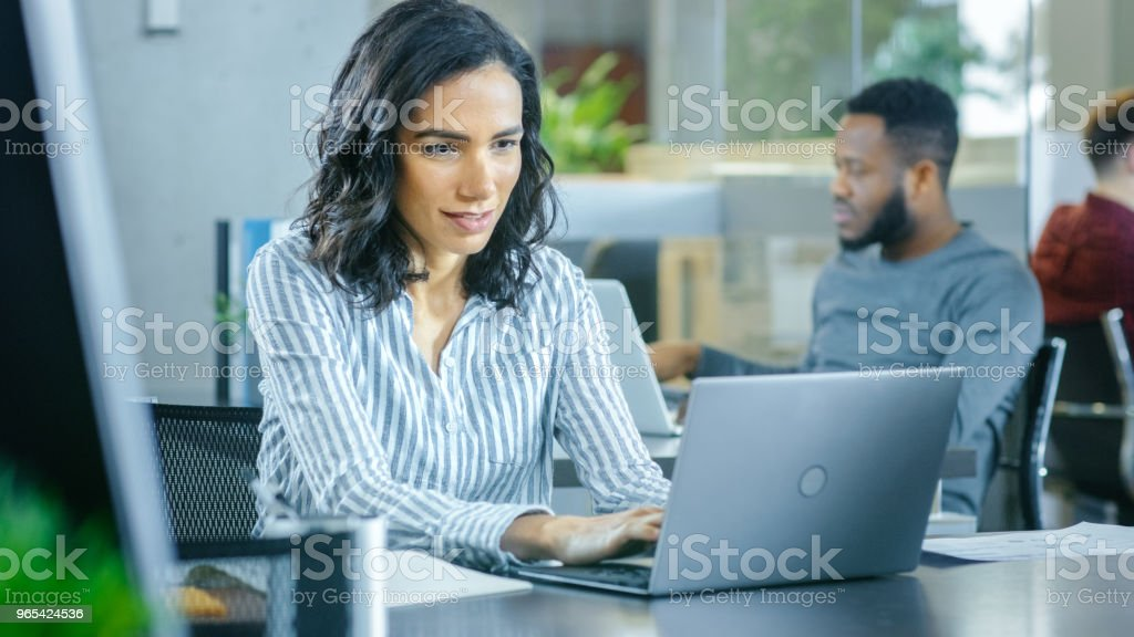 Busy International Office, Beautiful Hispanic Woman Working at Her Desk on a Laptop, in the Background Diverse Group of Creative Colleagues Working. royalty-free stock photo